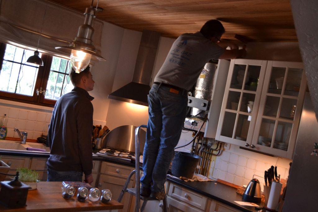 """Romain er i gang med at afmontere den gamle varmer, mens """"le jeune"""" ser på"""